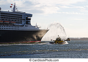 Fire fighting boat spraying jets of water when cruiseship...