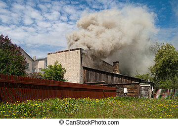fire in city building, with white smoke to the blue sky