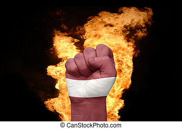 fire fist with the national flag of latvia