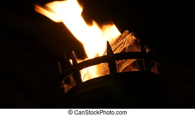 Fire flames in medieval torch on in the dark on black background close up view