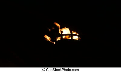 Fire flames in medieval torch on in the dark on black background