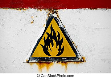 Fire hazard sign on an old metal surface