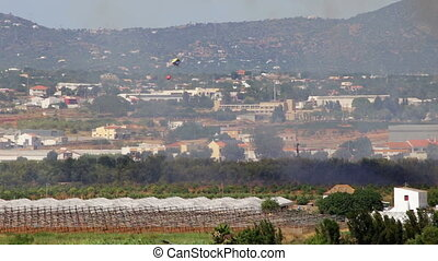 Fire helicopter, flying around the fields to extinguish a...