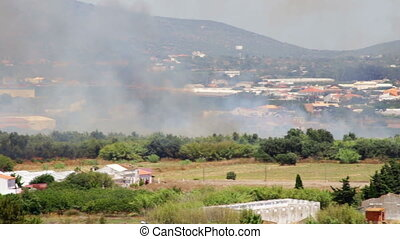 Fire helicopter pours water on a burning garden. Faro - Fire...