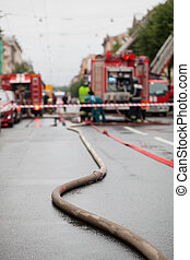 Fire hoses on the background of fire trucks and firefighters...