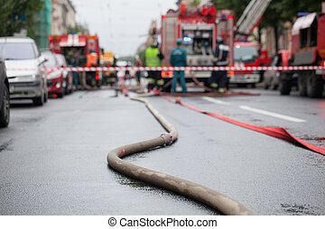 Fire hoses on the background of fire trucks and firefighters at work