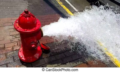 Fire hydrant gushing clean water flow in the streets