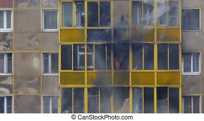 Fire in a residential building. Flames burst out through the balcony window. Firemen extinguish flame from ground. Slow motion.