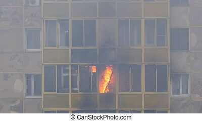 Fire in a residential building. Flames burst out through the balcony window. Slow motion.
