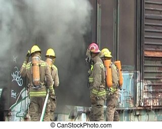 Fire in boxcar - Firemen putting out a fire in a railway car