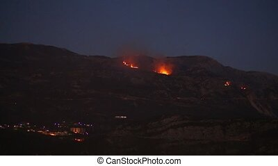 Fire in the mountains at night. Smoke over the mountains....