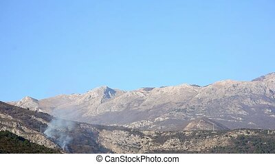 Fire in the mountains in the afternoon. Smoke over the...