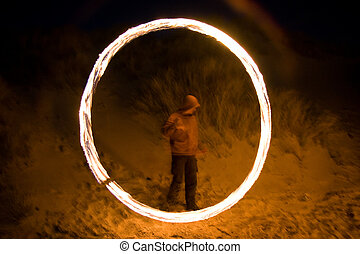 Fire juggling on a beach at night