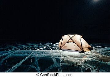 Fire on ice at night. Campground on ice. Tent stands next to bonfire. Lake Baikal. Nearby there is car. Shelter tent and ice are illuminated from the inside. Beautiful bonfire on real cracked ice.