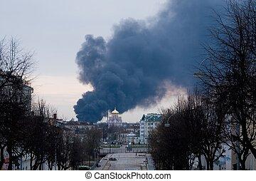 Fire. Black smoke curls above the city.