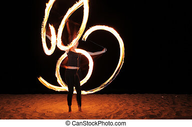 fire poi - a woman does a fire performance on the beach