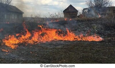 Fire rages in long grass, foreground against the background of wooden houses.