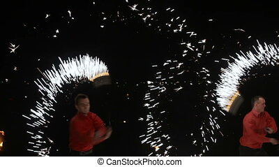 Fire show in the dark. - Men and women twist fiery circles...