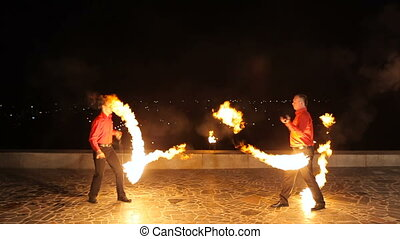 Fire show in the dark. - Men twist fiery circles on a fire...