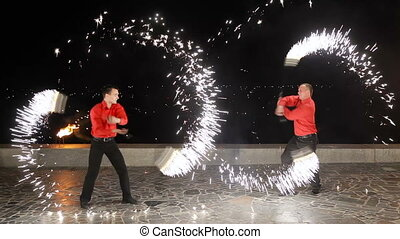 Fire show in the dark. - Men and women twist fiery circles...