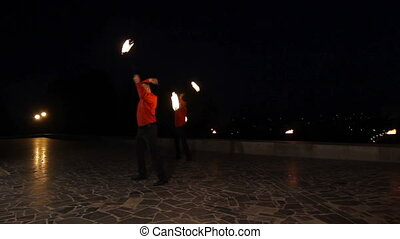 Fire show in the night. - Men twist fiery circles on a fire...