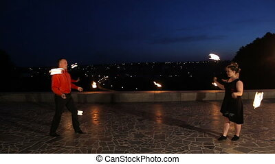 Fire show in the night. - Men and women artists twist fiery...