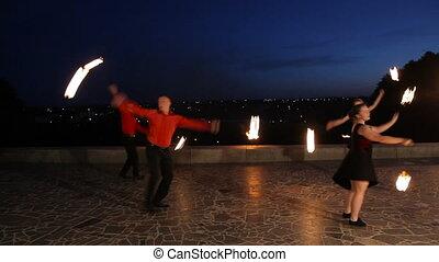 Fire show in the night. - Men and women artists twist fiery...