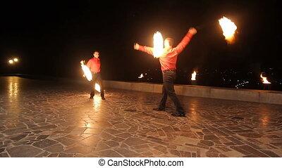 Fire show in the night. - Men artists twist fiery circles on...