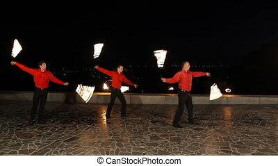 Fire show in the night. - Men twist fiery circles on a fire...