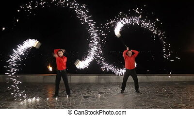 Fire show in the night. - Men and women twist fiery circles...