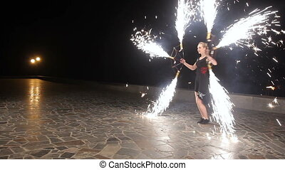 Fire show in the night. - Woman twist fiery circles on a...