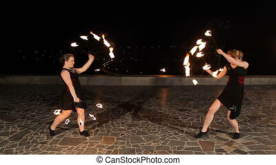 Fire show in the night. - Women artists twist fiery circles...