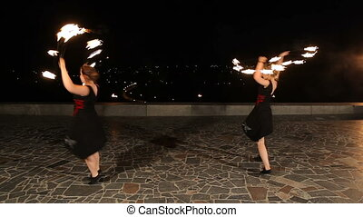 Fire show in the night. - Women artists twist fiery circles...