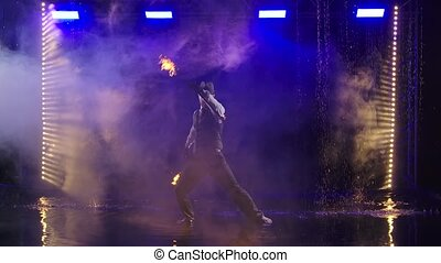 Fire show in the rain in the studio. Professional artist ...