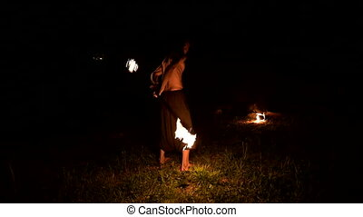 Fire show. Man juggles with two burning torches. Night show....