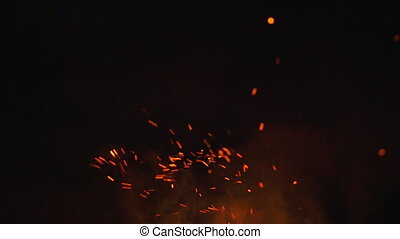 fire sparks from campfire over black background, slow motion...
