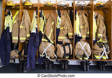 Helmets, boots and jackets in a fire station ready to be used by firefighters.