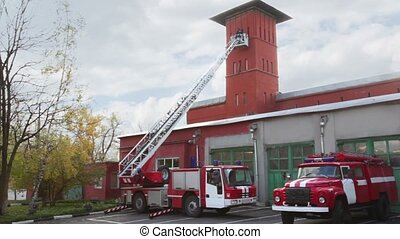Fire station, two red fire truck with long ladder, red high...