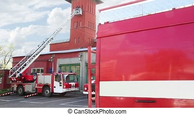 Fire station, two red fire truck with long ladder and a part of another one closer