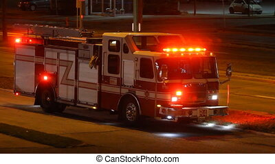 Firetruck is on the side of the road at night in the city