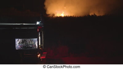 Fire truck on background of burning grass on field. - Fire...