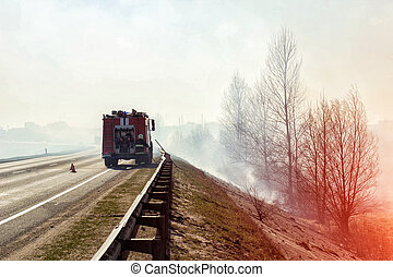 Fire truck with a firefighter on the road extinguishes a forest fire, heavy smoke, danger