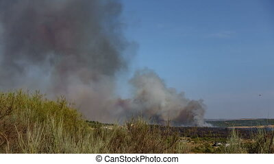 Fire with huge smoke near small village, time lapse -...