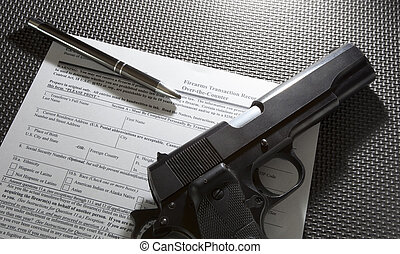 Handgun and pen and paperwork required for the background check for a gun purchase