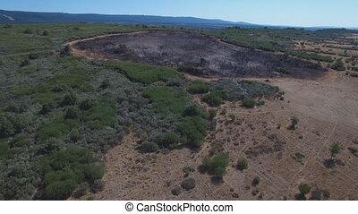Firebreak around burnt area, ascending camera