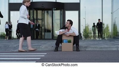 Fired businessman sitting on street