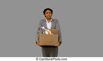 Fired businesswoman dropping a box on grey screen in slow...