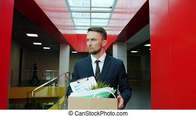 Fired clerk unhappy young man in suit is walking in hall leaving workplace with box of belongings feelings sad being unemployed. Dismissal and emotions concept.