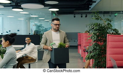 Fired employee walking in shared office with box of things ...