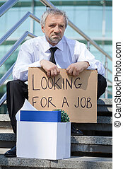 Fired man. Depressed senior man in formalwear holding a poster